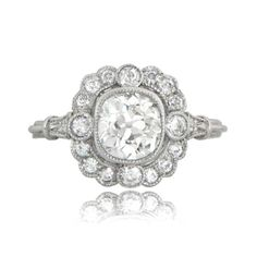 A beautiful vintage style engagement ring, adorned with a halo of diamonds and triple wire band. Beautiful filigree and milgrain add to the delicacy.