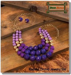 Radiant Orchid Jewelry Set - Three rows of dazzling orchid tonal faceted beads will make a stunning statement about your style! This pretty necklace also features golden beads that shimmer in the light, and the matching purple dangle earrings are the perfect complement.  Only $24.47 plus FREE shipping!