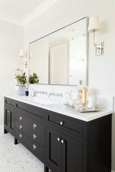 A gorgeous black bathroom vanity sits on maze marble floor tiles and is fitted with polished nickel ring pulls and a white marble countertop holding a trough sink under 2 wall mounted polished nickel faucets fixed on a marble backsplash beneath a metal fr Black Vanity Bathroom, Bathroom Faucets, Small Bathroom, Black Cabinets Bathroom, Granite Bathroom, Bathroom Bin, Mosaic Bathroom, Gold Bathroom, Double Mirror Vanity