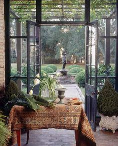 sunroom with steel doors and windows, brick floor, potted topiaries, gorgeous garden view - Louisana Plantation Home by Steichen Interior Design