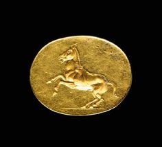 A GREEK GOLD FINGER RING   Circa 4th Century B.C.   The heavy, solid-cast ring with a plain hoop, rounded on the exterior and faceted on the interior, expanding at the shoulders to the large oval bezel, finely engraved with a rearing horse, the details of the musculature and of the mane well-rendered, the rear legs positioned on a short groundline