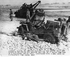Sur les galets d'Omaha Beach à marée basse : une jeep capot ouvert avec deux cadavres américains, deux GI's et un wrecker (camion de dépannage).  En arrière plan des obstacles de plage sur la gauche et des navires devant la plage.  Au Ruquet, le 7 juin 1944.