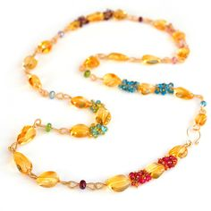 Smooth, golden citrine nuggets are connected by hand-coiled links and accented with a multitude of vibrant gemstone accents to include tourmaline, orange sapphires, pink sapphires, yellow sapphires, p