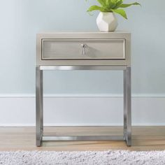 If the idea of functional goodness makes you smile as much as style does, meet our charismatic Riley Side Table. The updated design (modern, squared,    stainless steel frame in a chic, matte silver finish) enhances your room sense of space while adding the utility and accent style you need. Finely    colored ashwood veneer surfaces add more presence. And we love the nickel-finish metal tassel-motif hardware drawer trim we see winking at us like    furniture jewelry. The drawer behind tha...