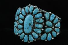 "Silver Zuni Petit Point Bracelet by silversmith Joe Wilson.  This is a beautiful bracelet fashioned from 62.5 grams of sterling silver by Zuni silversmith Joe Wilson, It features 35 tear shaped turquoise pieces approximatley 3/10"" in size and one center oval piece of turquoise approximatley 1"" x 1/2"".  SOLD!"
