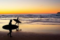 Two surfer running on the beach at sunset. Portugal has one of the best surfing scenes in Eu via MuralsYourWay.com