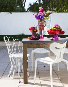 This mix and match of white outdoor design classic chairs is a great design statement. Combine rich reds and deep purples flowers & fruits for statement table decorations this summer. Image : Livingetc