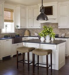 Chic country kitchen design with glazed ivory kitchen cabinets, tumbled stone tiles backsplash, stainless steel apron sink, honed black granite countertops, oil-rubbed bronze yoke pendant, bamboo roman shade and topiaries.