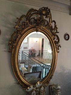 Important miroir ovale dans un encadrement en bois et stuc doré à
