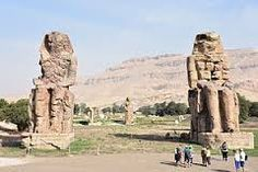 """Colossi of Amenhotep III - The historian Durant describes the grandeur of Amenhotep III monuments in writing, """"Two giants [sit] in stone, representing the most luxurious of Egypt's monarchs, Amenhotep III. Each is seventy feet high, weighs seven hundred tons, and is carved out of a single rock"""""""
