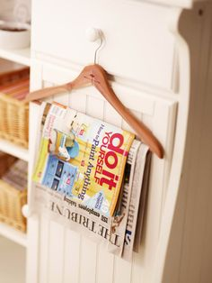 Piles of magazines and newspapers stack up easily and create clutter. Sort ones you still want to read, and use a sturdy wooden hanger to keep reading material within arms reach. Could be fun for bathroom reading. :)