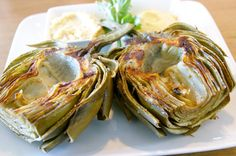 Ingredients: 3 whole artichokes 1 lemon 1 tablespoon salt 1 tablespoon whole peppercorns 4-6 cloves garlic 3 tablespoons olive oil If using a grill that needs to be started ahead...