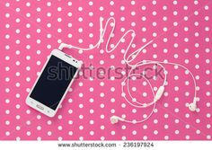Small headphones with mobile phone on pink vintage paper with dots - stock photo