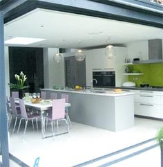 Extensive use of glazing and folding-sliding doors mean the kitchen extension blends seamlessly into the garden