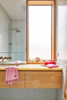 It might be a small bathroom, but what it lacks in size it makes up for in style. Cool concrete is warmed up with timber drawers and the natural light of a slim window.