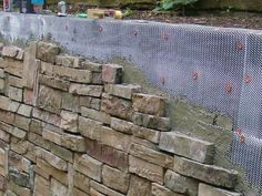 DIYNetwork.com experts give a railroad-tie retaining wall a new facing of stylish stonework.