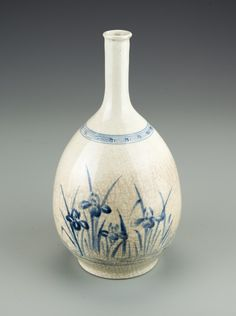A Korean Blue and White Vase, 17th Century. The vase with a slightly flared mouth, slender neck and bottom-heavy body resting on a circular foot ring, the vase painted in underglaze blue on a crackle ground that gradually darkens toward the base, with a mark to the base. 9 1/2 by 4 5/8 in.