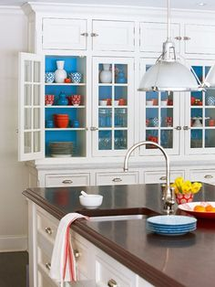 In an all-white kitchen, painting the interior of glass-front or open cabinetry makes a dramatic background for kitchenware and collectibles. A bold shade of blue is the perfect backdrop for this kitchen. via: house design design interior design All White Kitchen, White Kitchen Cabinets, New Kitchen, Kitchen Decor, Kitchen Storage, Blue Cabinets, Kitchen Cabinetry, Kitchen Paint, Kitchen Shelves