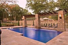 Swimming Pool with Covered Patio - A trio of stacked-stone columns not only overlooks the poolscape, but also act as water and fire features.  Photo courtesy of Aquatech Society: Baker Pools http://www.luxurypools.com/