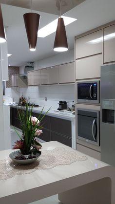 Cozinha - projeto especial de marcenaria produzido em laca brilhante em tons neutros, torre de eletros, e destaque para a cuba de quartzo preta da tramontina