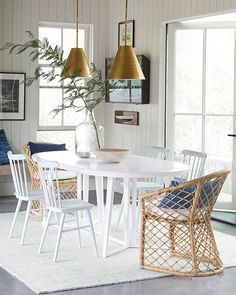We love this crisp white dining room with woven rattan chairs, classic wooden chairs, an oval dining table, and brass light pendants. White Dining Table, Small Dining, Dining Room Table, Dining Chairs, Rattan Chairs, Wooden Chairs, Blue Chairs, White Chairs, Room Chairs