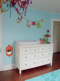 Simple dresser doing double duty as a  changing table.  PS Look UP and check out that awesome chandelier!! :)
