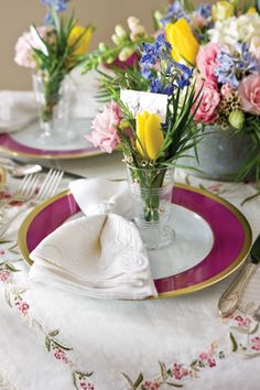 Place cards perch atop small floral arrangements in dainty glasses.