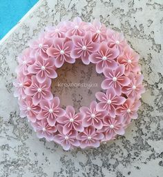 Origami Paper Flower Wreath!  This beautiful Origami Flower Wreath would be a stand out on your front door!! This could be used as a centerpiece, candle decor or used as party decor. This would also be the perfect gift for that someone special! The possibilities are endless!  This wreath has 3 rows of origami flowers made from Vellum specialty scrapbook paper that are cut into 3x3 then folded into a petal to be combined to make a beautiful flower. The span of the flower is approx 3. They are…