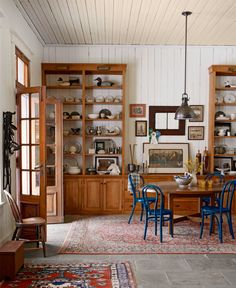 Built-in shelves contain china platters and dinnerware, antique silver and pewter, and vintage duck decoys.