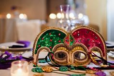 Jester mask and mardi gras doubloons for a mardi gras wedding tablescape.