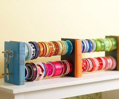 Ribbon Holders by the Book  Drill two sets of holes through three old books for an interesting way to display your ribbon. Thread ribbon on wooden dowels and push the dowels through the holes. Hang scissors or other crafting essentials on the ends.