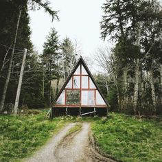a-frame glass cabin in the woods