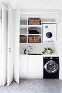 As portas tipo sanfona ocultam a lavanderia estilosa, localizada no corredor da casa. Para quebrar a predominância do branco, a máquina de lavar e os puxadores são pretos.