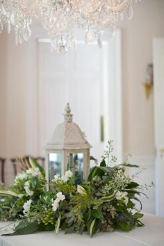 lantern with mixed greens as centerpiece....lovely for a wedding or shower
