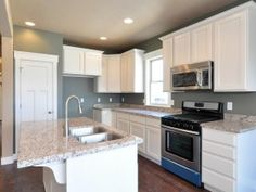 Love the white cabinets and greenish/gray wall color