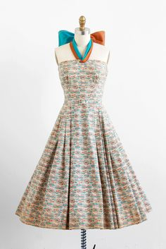 1950s paisley cotton dress with enormous halter-neck bow tie. Sash loops through a buttonhole at the neckline + ties in a bow at the back of the neck; brown on one side + blue on the other side.