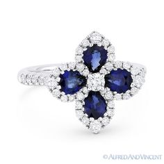 The featured flower-design ring is cast in 18k white gold and showcases a flower design petaled with pear-shaped blue sapphires and accentuated by round cut diamonds all the way around the flower and halfway along the band.