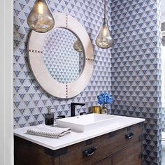 Posh prints and a pretty powder room from Ashley Campbell Interior Design ・・・ I adore this powder room from our modern farmhouse client!  From the Holland and Sherry Interiors printed grass cloth wallpaper, to the Jamie Young Co hair-on-hide mirror, to the to the semi-recessed sink, this powder room design is on point!