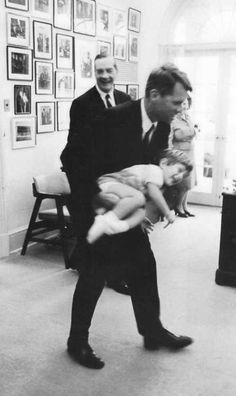 Bobby Kennedy tossing his nephew, John Jr., in White House, Oct. 1963.