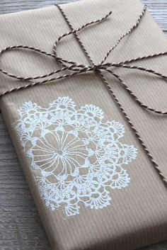 White lace stamp prints onto brown paper - the site also shows them on brown home made Christmas cards, which looks pretty also