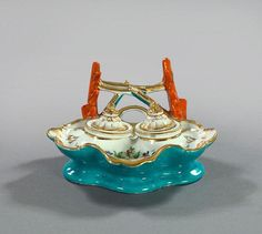 """Paris Porcelain Encrier, in the manner of Jacob Petit, second quarter 19th century, the shell-form tray outlined in gold and painted with flowers and containing a covered sander and ink pot, the pen holder in the form of coral, the underside glazed in celeste bleu, h. 3-1/2"""", w. 7"""", d. 6-1/2""""."""