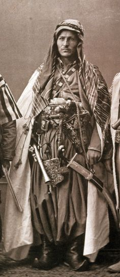 """Christian Maronite of Mount Lebanon, wearing a holster (kuberluk) with two pistols (kuber), a pala kilij sword and a blunderbuss. The Maronites lived under the authority of a Christian Pasha, sent from Constantinople to rule the Jebel-i-Lubnan (Mount Lebanon region). From:Les costumes populaires de la Turquie en 1873, 74 photographic plates by Pascal Sebah, published by the Imperial Ottoman Commission for the """"Exposition Universelle"""" of Vienna in 1873."""