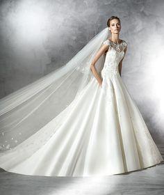 Vestido de novia, de raso de estilo princesa con aplicaciones de encaje, pedrería y flores. Cuerpo con canesú de escote barco y transparencia de escote corazón. Gran falda de raso fruncida en la espalda.