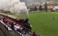 El tren pasa por un estadio de Eslovaquia. El tren que pasa por un campo de fútbol Un tren pasa entre el terreno de juego y la grada en el campo del club TJ Tatran Cerny Balog de Eslovaquia