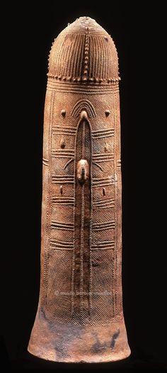 Pseudo calice funéraire  Niger, site de Bura-Asinda-Sikka Culture de Bura 14ème - 17ème siècle (TL) Terre cuite, restauration de la base H. : 95 cm ; diam. : 30 cm INV. 1016-3 Ce haut vase tubulaire, dont l'ouverture est conçue comme une base, constitue la partie inférieure d'une « effigie funéraire ». Celle-ci devait autrefois être composée d'une statuette anthropomorphe ou d'un cavalier de terre cuite fixé au sommet du pseudo-calice, endossant dès lors le rôle de piédestal. Des cénotap