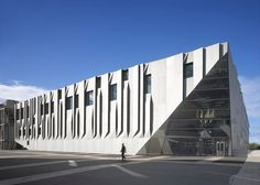 Folded aluminium panels create vertical and horizontal pleats across the walls of this music conservatory and concert hall completed by Kengo Kuma.