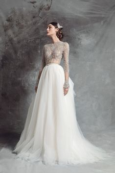 Nude tulle bodice with cut out silver French embroidery decorated with mounted crystals. Long sleeves and embroidered waistband. Soft tulle skirt.