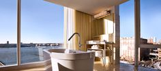 The exposed bathroom's freestanding tub soaks in views in a Hudson Studio, The Standard New York