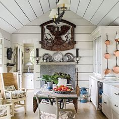 With the stone fireplace, the walls and ceiling clad in painted boards, and the cabinets made from salvaged window sashes, the renovated kitchen exudes old-farmhouse charm.