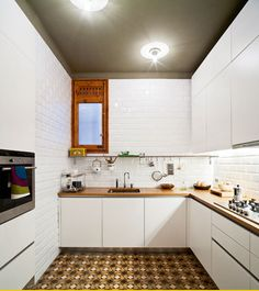 kitchen - painted dark grey ceiling, white cabinets, white subway tile walls and back splash, butcher block counter, unique tile floor